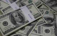 Пачки долларовых купюр в банке в Сеуле 2 августа 2013 года. Sysco Corp купит конкурента US Foods Inc примерно за $3,5 миллиарда и возьмет на себя долги компании в размере $4,7 миллиарда в попытке укрепить лидерство в сфере продажи продуктов питания в США. REUTERS/Kim Hong-Ji