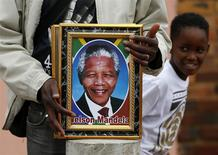 A street vendor sells portraits of Nelson Mandela on Vilakazi Street in Soweto, where the former South African president resided when he lived in the township, December 9, 2013. REUTERS/Yves Herman