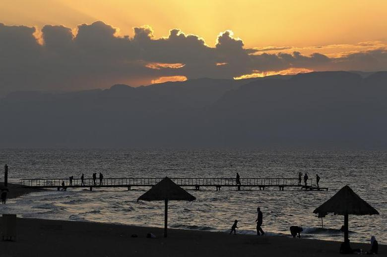 People are seen as the sun sets over a beach in the Aqaba Gulf on the Red Sea, south of Amman November 25, 2011. Picture taken November 25, 2011. REUTERS/Muhammad Hamed