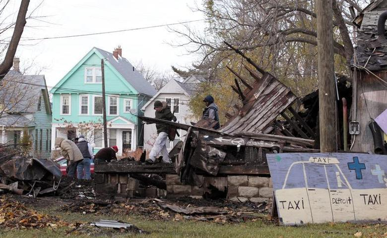 People try to save remains from a vacant house that was covered with hundreds of vinyl LP music albums, known as the 'House of Soul', that is part of the internationally known Heidelberg Project outdoor art installation by artist and founder Tyree Guyton in Detroit, Michigan November 12, 2013. REUTERS/Jeff Kowalsky