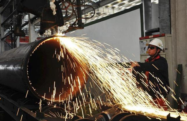 A worker operates a machine to cut a pipeline at a factory in Qingdao, Shandong province November 29, 2013. REUTERS/China Daily