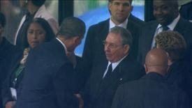 U.S. President Barack Obama (2nd L) shakes hands with Cuban President Raul Castro (C) in this still image taken from video courtesy of the South Africa Broadcasting Corporation (SABC) at the First National Bank (FNB) Stadium, also known as Soccer City, during former South African President Nelson Mandela's national memorial service in Johannesburg December 10, 2013. Obama shook the hand of Castro at a memorial to Mandela on Tuesday, an unprecedented gesture between the leaders of two nations which have been at loggerheads for more than half a century. REUTERS/SABC via Reuters TV