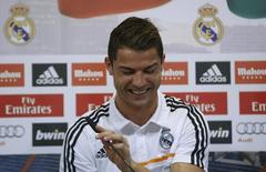 Real Madrid's Cristiano Ronaldo reacts as he attends a news conference to discuss the draw for the 2014 World Cup at the Valdebebas training grounds, outside Madrid, December 8, 2013. REUTERS/Javier Barbancho