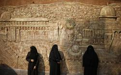 Palestinian women stand in front of a mural depicting al-Aqsa mosque during a protest against the blockade on the Gaza Strip, in Gaza City November 19, 2013. REUTERS/Suhaib Salem