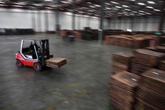 Foto del 23 de marzo de 2012. Un trabajador traslada cátodos de cobre a un almacén cerca de Yangshan Deep Water Port, al sur de Shanghái. La producción de cobre refinado de China subió un 2,6 por ciento en noviembre frente a octubre y alcanzó un récord por tercer mes consecutivo debido a un incremento de las ganancias en fundiciones, mientras que al aluminio primario también anotó un récord por segundo mes seguido. REUTERS/Carlos Barria
