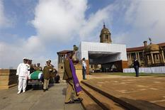 Military personnel carry the remains of the late Nelson Mandela upon arrival at the Union Buildings in Pretoria, December 11, 2013, as members of the Mandela family follow behind. REUTERS/Kim Ludbrook/Pool