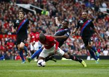Manchester United's Ashley Young (L) is fouled by Crystal Palace's Kagisho Dikgacoi during their English Premier League soccer match at Old Trafford in Manchester, northern England September 14, 2013. REUTERS/Darren Staples