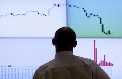 Сотрудник биржи РТС стоит перед экраном с рыночными котировками и графиками в Москве 11 августа 2011 года. Российские акции, открыв сессию четверга уверенным снижением по всему спектру бумаг, не изменили динамики к середине торгов. REUTERS/Denis Sinyakov