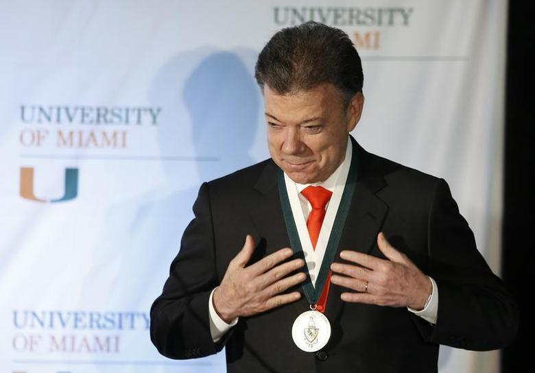 Colombia's President Juan Manuel Santos reacts after he received the 'President's Medal' from University of Miami President Donna Shalala during his visit to the University in Coral Gables, Florida December 2, 2013. REUTERS/Joe Skipper