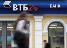 Женщина проходит мимо отделения банка ВТБ 24 в Москве 3 апреля 2013 года. Российские госбанки начали пожинать плоды в сегменте потребкредитования, где лидирующие на этом рынке банки-монолайнеры теряют позиции, притормаживая рост бизнеса под гнетом регулирования ЦБР. REUTERS/Sergei Karpukhin