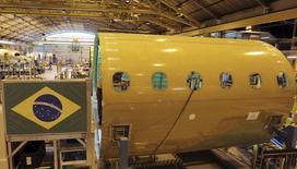 Funcionário trabalha na linha de montagem de jatos na sede da Embraer em São José dos Campos. A Embraer, terceira maior fabricante mundial de aviões civis, recebeu da norte-americana American Airlines um pedido de encomendas firmes por 60 aviões E175, um negócio estimado em 2,5 bilhões de dólares a preços de tabela. 14/05/2013 REUTERS/Nacho Doce