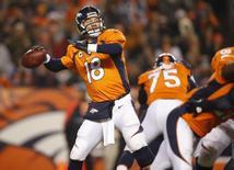 Jogador do Denver Broncos Peyton Manning lança a bola durante partida contra o San Diego Chargers em jogo da NFL, no estádio Sport Authority Field, em Denver. Quatro pessoas foram esfaqueadas, uma delas ferida com gravidade, em uma briga na noite de quinta-feira no estacionamento do estádio onde acontecia a partida pela liga de futebol americano dos EUA (NFL), disse a polícia. 8/12/2013. Chris Humphreys-USA TODAY Sports