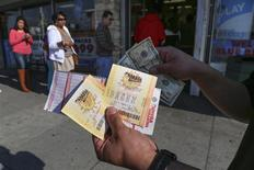 A man shows his recently purchased Mega Millions lottery tickets at Bluebird Liquor in Hawthorne, California December 13, 2013. REUTERS/Jonathan Alcorn