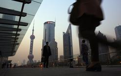People walk along an elevated walkway at the Pudong financial district in Shanghai November 20, 2013. REUTERS/Carlos Barria