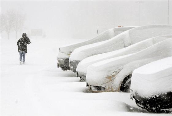 An employee walks to her vehicle in heavy snow in the parking lot of New Era Cap Company in Evans, New York, December 11, 2013. REUTERS-Don Heupel