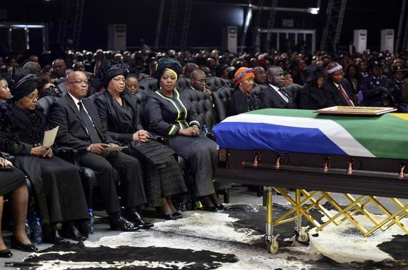 South Africa's President Jacob Zuma (2nd L), the ex-wife of former South African President Nelson Mandela, Winnie Mandela (L), and the widow of Mandela, Graca Machel (3rd L), sit by the coffin of Mandela during his funeral ceremony in Qunu December 15, 2013. REUTERS-Odd Andersen-Pool