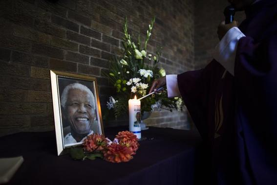A priest lights a candle in memory to former South African President Nelson Mandela at the Regina Mundi Church during Sunday service in Soweto, December 15, 2013. REUTERS-Ronen Zvulun