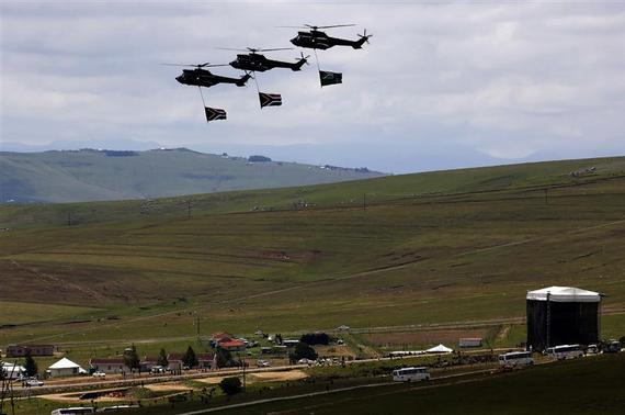 Army helicopters carry South African flags over the burial ground of late former South African President Nelson Mandela during his funeral in Qunu, December 15, 2013. REUTERS-Yannis Behrakis