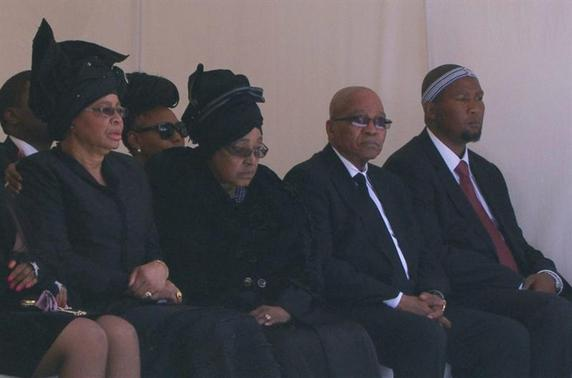 From L-R: Graca Machel, widow of former South African President Nelson Mandela, Winnie Mandela, ex-wife of Mandela, South African President Jacob Zuma and Mandela's grandson Mandla Mandela sit at his burial site in his ancestral village of Qunu in the Eastern Cape province, 900 km (559 miles) south of Johannesburg, in this still image taken from December 15, 2013 video courtesy of the South Africa Broadcasting Corporation (SABC). REUTERS-SABC via Reuters TV