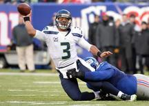 Dec 15, 2013; East Rutherford, NJ, USA; Seattle Seahawks quarterback Russell Wilson (3) throws a pass as he is taken down by New York Giants defensive tackle Linval Joseph (97) in the first half during the game at MetLife Stadium. Mandatory Credit: Robert Deutsch-USA TODAY Sports - RTX16JZ7