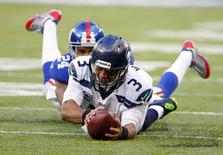 Dec 15, 2013; East Rutherford, NJ, USA; Seattle Seahawks quarterback Russell Wilson (3) dives forward for a first down as New York Giants cornerback Terrell Thomas (24) catches him from behind during the first half at MetLife Stadium. Mandatory Credit: Jim O'Connor-USA TODAY Sports - RTX16K72