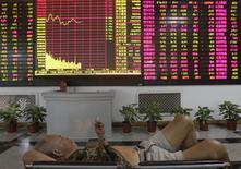 Инвестор лежит на скамейке в помещении брокерской конторы в Ухане 22 августа 2012 года. Регуляторы рынка ценных бумаг Китая опубликовали новые подробности возобновления первичных публичных размещений акций (IPO) в начале следующего года, отменив контроль за ценообразованием и оборотом и объяснив, как будет осуществляться участие инвесторов. REUTERS/Stringer