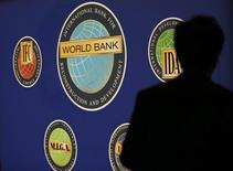 Силуэт мужчины на фоне логотипа Всемирного банка в Токио 10 октября 2012 года. Всемирный банк сократил прогноз роста ВВП России на 2013 и 2014 годы, сославшись на низкие инвестиции и не оправдавший ожидания спрос потребителей - главные двигатели экономики страны. REUTERS/Kim Kyung-Hoon