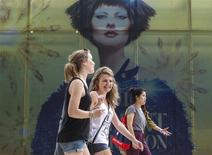 Tourists walk pass a billboard near a department store in Bangkok December 16, 2013. REUTERS/Athit Perawongmetha