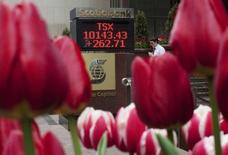 A man walks past a sign displaying TSX information is seen in Toronto, May 6, 2009. REUTERS/Mark Blinch