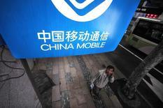 Placa da China Mobile em rua do centro de Xangai. Apesar de toda a expectativa, o muito aguardado acordo da Apple com a China Mobile pode resultar em pouco mais que um impulso momentâneo nas receitas da gigante norte-americana. Um acordo com a maior operadora de telefonia móvel do mundo, esperado para esta semana, dá à Apple 759 milhões de novos potenciais consumidores que poderiam gerar 3 bilhões de dólares em receita em 2014, ou quase um quarto do crescimento projetado de receita da Apple em seu atual ano fiscal. 22/10/2012. REUTERS/Carlos Barria