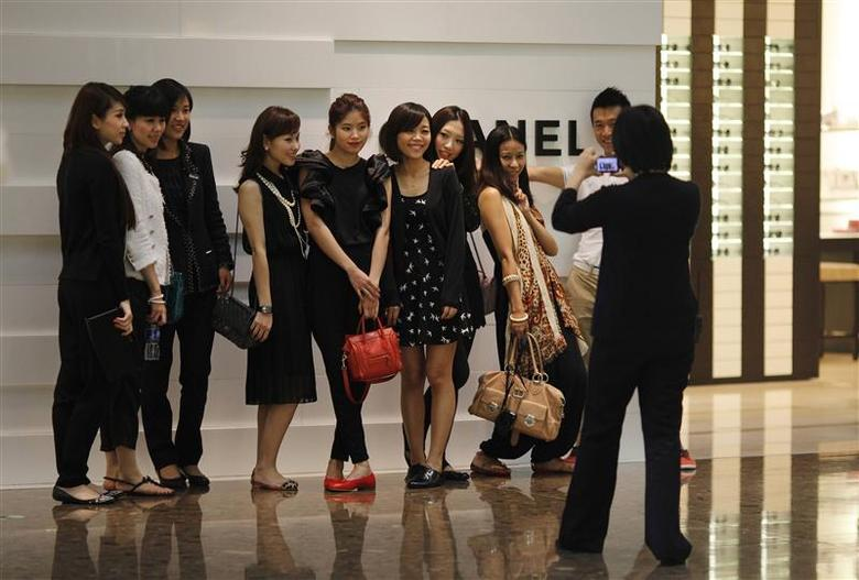 Shoppers pose for a picture in front of a Chanel luxury boutique at the IFC Mall in Shanghai, in this June 4, 2012 file picture. REUTERS/Carlos Barria