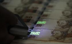 Funcionário verifica folhas de papel moeda durante visita da mídia à Casa da Moeda, no Rio de Janeiro. O Índice Geral de Preços-10 (IGP-10) subiu 0,44 por cento em dezembro, mesma alta de novembro, acumulando no ano elevação de 5,39 por cento, informou nesta segunda-feira a Fundação Getulio Vargas (FGV). 23/08/2012 REUTERS/Sergio Moraes