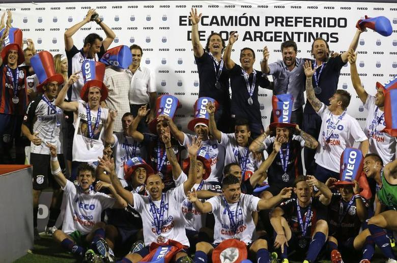 San Lorenzo's players celebrate clinching the Argentine First Division championship at the end of their soccer match against Velez Sarsfield in Buenos Aires December 15, 2013. REUTERS/Enrique Marcarian