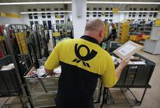 A postman of the German postal and logistics group Deutsche Post sorts mail at a sorting office in Berlin's Mitte district, December 4, 2013. REUTERS/Fabrizio Bensch