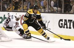 Boston Bruins right wing Shawn Thornton (22) is chased by Chicago Blackhawks center Michal Handzus (26) during the first period in Game 3 of their NHL Stanley Cup Finals hockey series in Boston, Massachusetts, June 17, 2013. REUTERS/Winslow Townson