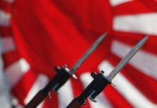 Винтовки с примкнутыми штык-ножами на фоне флага императорского флота Японии во время ежегодного смотра войск на базе в Асаке 27 октября 2013 года. Япония увеличит военные расходы и укрепит отношения с союзниками на фоне растущей напряжённости в отношениях с Китаем из-за спорных островов Восточно-Китайского моря. REUTERS/Issei Kato