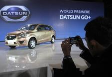 Посетитель презентации в Джакарте фотографирует Datsun GO 17 сентября 2013 года. Японский автоконцерн Nissan начнет продажи бюджетного автомобиля Datsun в августе-сентябре следующего года, обещая продавать его не дороже 400.000 рублей ($12.100), сообщил журналистам во вторник директор Datsun в России Жером Сего. REUTERS/Supri