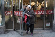 People carrying shopping bags leave a shopping store advertising sales in New York, December 24, 2012. REUTERS/Keith Bedford