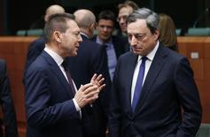 Le ministre des Finances grec Yannis Stournaras aux côtés du présidnet de la BCE Mario Draghi (à droite), à Bruxelles à l'occasion d'un sommet des ministres des Finances de la zone euro. La zone euro va accorder un milliard d'euros à la Grèce cette semaine dans le cadre de son plan de sauvetage international. /Photo prise le 17 décembre 2013/REUTERS/François Lenoir