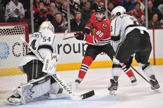Dec 15, 2013; Chicago, IL, USA; Chicago Blackhawks right wing Patrick Kane (88) shoots the puck against Los Angeles Kings goalie Ben Scrivens (54) during the third period at the United Center. The Blackhawks won 3-1. Mandatory Credit: Rob Grabowski-USA TODAY Sports - RTX16KHI