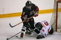 Japan's Tomoko Sakagami (L) fights for the puck with Switzerland's Katrin Nabholz during a round two game at the IIHF Women's World Ice Hockey Championships in Hameenlinna April 9, 2009 file photo. REUTERS/Bob Strong