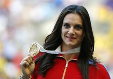 Gold medallist Yelena Isinbayeva of Russia holds her medal at the women's pole vault victory ceremony during the IAAF World Athletics Championships at the Luzhniki stadium in Moscow August 15, 2013. REUTERS/Denis Balibouse