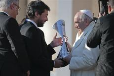 A member of Argentine soccer team San Lorenzo presents Pope Francis (R) with the replica of the trophy that they won in the Argentine soccer championship, during the Wednesday general audience in Saint Peter's square at the Vatican December 18, 2013. REUTERS/Tony Gentile