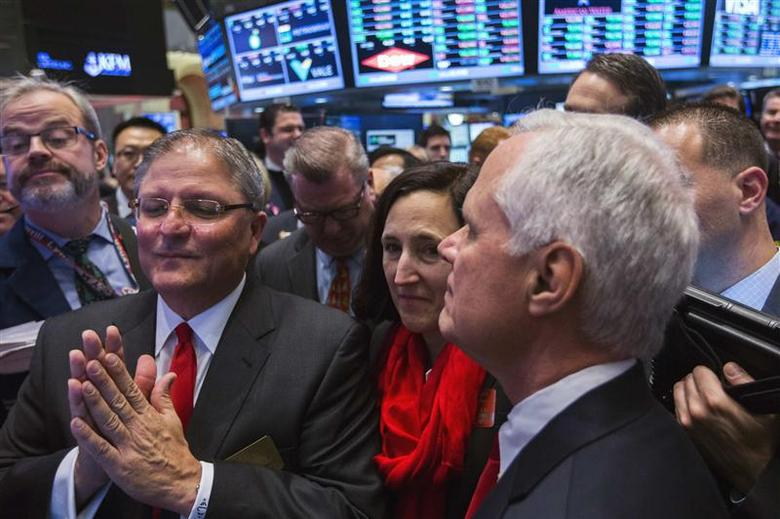Gerardo Lopez (L), AMC Entertainment CEO & president, reacts with Executive Vice President, Elizabeth Frank (C), and AMC Executive Vice President, Craig R. Ramsey, applauds after the announcement of the price for their IPO on the floor the New York Stock Exchange December 18, 2013. REUTERS/Lucas Jackson