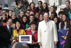 """Pope Francis poses with members of musical group """"Up with People"""" during his Wednesday general audience in Saint Peter's square at the Vatican December 18, 2013. REUTERS/Tony Gentile"""