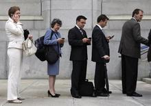 People use mobile devices while waiting to enter the Supreme Court of Canada in Ottawa June 17, 2008. REUTERS/Chris Wattie