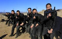 Students holding replica 95 semi-automatic rifles practice protecting their employers at a shooting training field managed by the military during Tianjiao Special Guard/Security Consultant training on the outskirts of Beijing December 14, 2013. REUTERS/Jason Lee