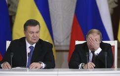 Лидеры Украины и России Виктор Янукович и Владимр Путин на церемонии подписания совместных документов в московском Кремле 17 декабря 2013 года. Украина могла получить от Евросоюза по меньшей мере 19 миллиардов евро ($26 миллиардов) кредитов и грантов в ближайшие семь лет, если бы в соответствии с ожиданиями подписала с блоком договор о торговле и сотрудничестве, свидетельствуют внутренние данные ЕС. REUTERS/Sergei Karpukhin