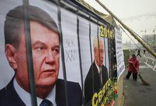 """Волонтёр подметает территорию рядом с палатками на киевском """"евромайдане, на которых помещены изображения президента Украины Виктора Януковича и премьер-министра Николая Азарова 18 декабря 2013 года. Янукович, чья популярность пошатнулась из-за решения развернуться от ЕС к России, приведшего к массовым уличным протестам, сказал, что откажется от претензий на второй срок, если его рейтинг останется низким. REUTERS/Gleb Garanich"""