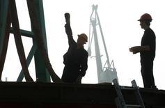 Рабочие участвуют в процессе погрузки на баржу колеса турбины для дальнейшей транспортировки на место строительства Саяно-Шушенской ГЭС 3 августа 2011 года. Основной регулятор российского энергорынка Совет рынка разрешил госкомпании Русгидро перенести сроки достройки затопленной из-за сентябрьской аварии ГАЭС в Подмосковье на три года без оплаты штрафа, сообщили представители организации. REUTERS/Ilya Naymushin